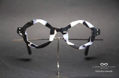 Monture noir et blanche avec verre en forme d'hexagone